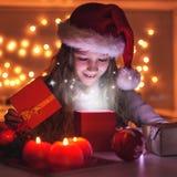 El niño abre un regalo del ` s del Año Nuevo Fotografía de archivo