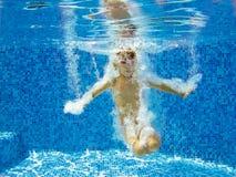 El niño activo feliz salta a la piscina Imagenes de archivo