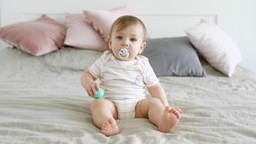 El niño adorable con los ojos azules hermosos se está sentando en la cama que chupa en el maniquí almacen de video