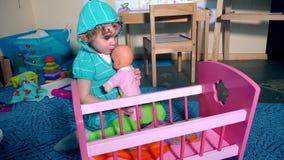 El niño adorable mece al bebé de la muñeca del oscilación cerca de cama del pesebre del juguete metrajes
