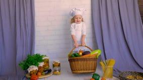 El niño adorable sonriente levanta la cesta con la comida sana, verduras Concepto sano de la consumición
