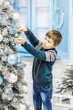 El niño adorna el árbol de navidad Muchacho Año Nuevo del concepto, Merr Imagen de archivo