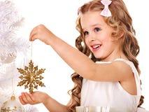 El niño adorna el árbol de navidad. Imagen de archivo