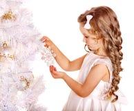 El niño adorna el árbol de navidad. Foto de archivo