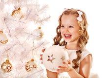 El niño adorna el árbol de navidad blanco. Fotografía de archivo