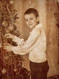 El niño adorna en el árbol de navidad Foto de archivo