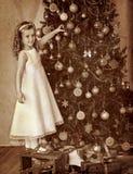 El niño adorna en el árbol de navidad Imagenes de archivo