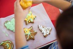 El niño adorna las galletas de la Navidad Imágenes de archivo libres de regalías
