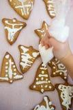 El niño adorna las galletas de la Navidad Imagen de archivo