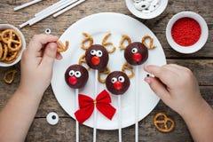 El niño adorna las galletas y el caramelo festivos de los estallidos de la torta del reno Imagen de archivo libre de regalías