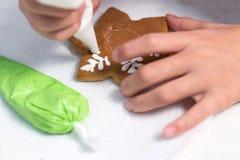 El niño adorna el pan de jengibre hecho a mano de la Navidad con el esmalte Galletas bajo la forma de copo de nieve Primer Imágenes de archivo libres de regalías