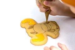 El niño adorna el pan de jengibre hecho a mano de la Navidad con el esmalte Galletas bajo la forma de figura de los ciervos o de  Fotos de archivo libres de regalías