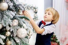 El niño adorna un árbol de navidad en el cuarto Invierno del concepto Fotografía de archivo