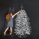 El niño adorna un dibujo del árbol de navidad en la pizarra Christma Imágenes de archivo libres de regalías