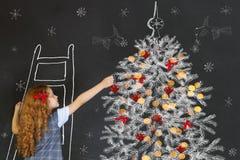 El niño adorna un dibujo del árbol de navidad en la pizarra Christma Fotografía de archivo