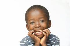 El niño africano de risa lleva a cabo su cabeza mientras que piensa al muchacho del negro de la pertenencia étnica de África Imagen de archivo