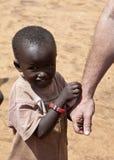 El niño africano lleva a cabo la mano del trabajador de ayuda Imagen de archivo
