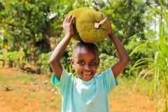El niño africano que juega con las frutas de sus padres cultiva en una calle en Kampala foto de archivo