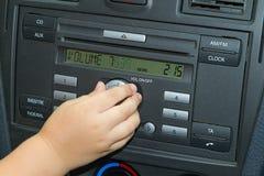El niño ajusta el volumen de radio de coche Fotos de archivo