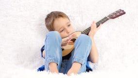 El ni?o al principio cogi? la guitarra ac?stica de los ni?os incorrectamente, despu?s le dio la vuelta y comenz? a jugar, sonrien metrajes