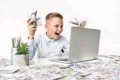 El niño alegre está ganando efectivo por Internet Imagen de archivo