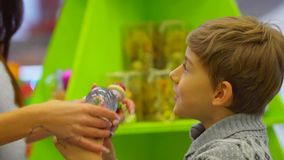 El niño alegre está mostrando a su madre la bola de la nieve en el centro comercial durante días de fiesta de la Navidad almacen de video