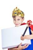 El niño alegre hermoso vestido como rey con una corona sostiene una bandera blanca rectangular Imagen de archivo