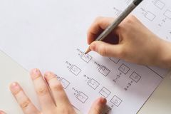 El niño anota respuestas para calificar los problemas de matemáticas uno; fotografía de archivo libre de regalías