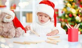 El niño antes de la Navidad escribe una letra a Papá Noel Fotos de archivo libres de regalías