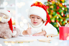 El niño antes de la Navidad escribe una letra a Papá Noel Imagen de archivo
