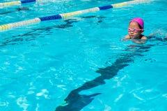 El niño aprende cómo nadar en clase de la natación fotografía de archivo libre de regalías