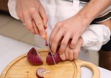 El niño aprende cortar verduras Foto de archivo libre de regalías