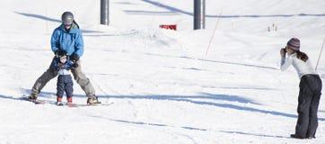 El niño aprende esquiar con el papá mientras que la mamá toma una foto imágenes de archivo libres de regalías