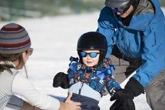 El niño aprende esquiar con el papá mientras que los relojes de la mamá Vestido con seguridad Imágenes de archivo libres de regalías