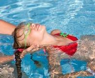 El niño aprende nadada en piscina. Imagenes de archivo