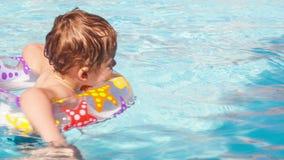 El niño aprende nadar usando un anillo plástico del agua metrajes
