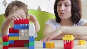 El niño, así como su madre, construye una casa de los bloques coloreados de Lego en la tabla Desarrollo infantil almacen de metraje de vídeo
