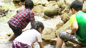 El niño asiático del OS del grupo se sienta y juega en el río almacen de metraje de vídeo