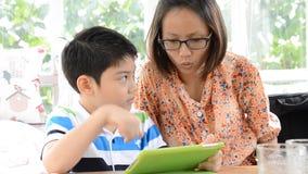 El niño asiático enarbola su atención de los niños con algo en una tableta electrónica con la madre almacen de video