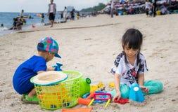 El niño asiático está jugando con la salvadera Fotos de archivo