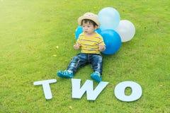 El niño asiático feliz del primer se sienta en piso de la hierba en fondo texturizado parque en el 2do concepto del aniversario d Fotos de archivo libres de regalías