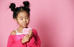 El niño asiático joven feliz de la niña se lame come el caramelo dulce grande feliz del lollypop en rosa imagenes de archivo