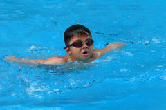 El niño asiático nada en piscina - el estilo de la mariposa toma la respiración profunda Foto de archivo libre de regalías