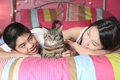 El niño asiático pone en su dormitorio con el gato Imagen de archivo libre de regalías