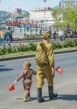 El niño bajo la forma de desfile militar, con los padres celebración del desfile del día de la victoria el 9 de mayo Vladivostok, Foto de archivo libre de regalías