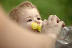 El niño bebe el agua Agua potable del bebé Foto de archivo libre de regalías