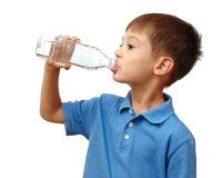 El niño bebe el agua de la botella foto de archivo