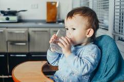 El niño bebe el agua de un vidrio fotografía de archivo