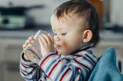 El niño bebe el agua de un vidrio foto de archivo