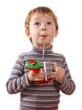 El niño bebe el jugo Foto de archivo